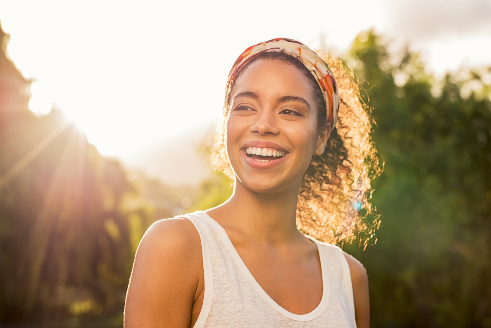 woman smiling and looking away at park during sunset