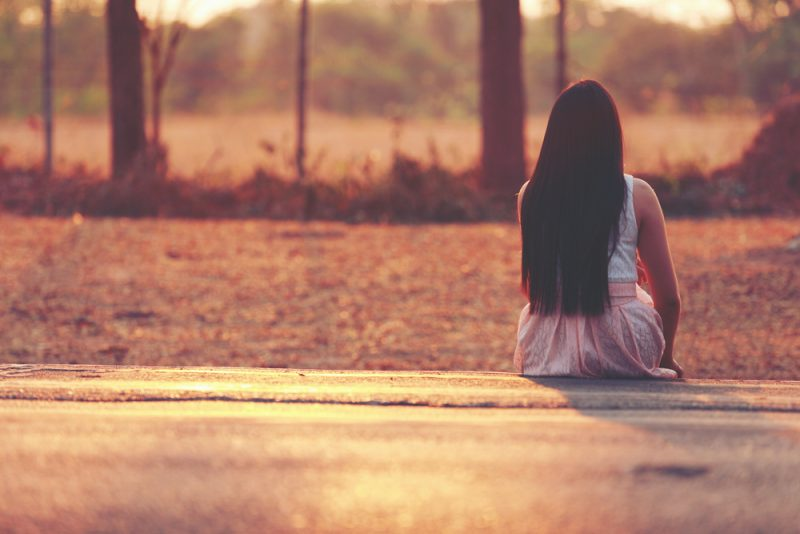woman with long hair sitting alone outdoor