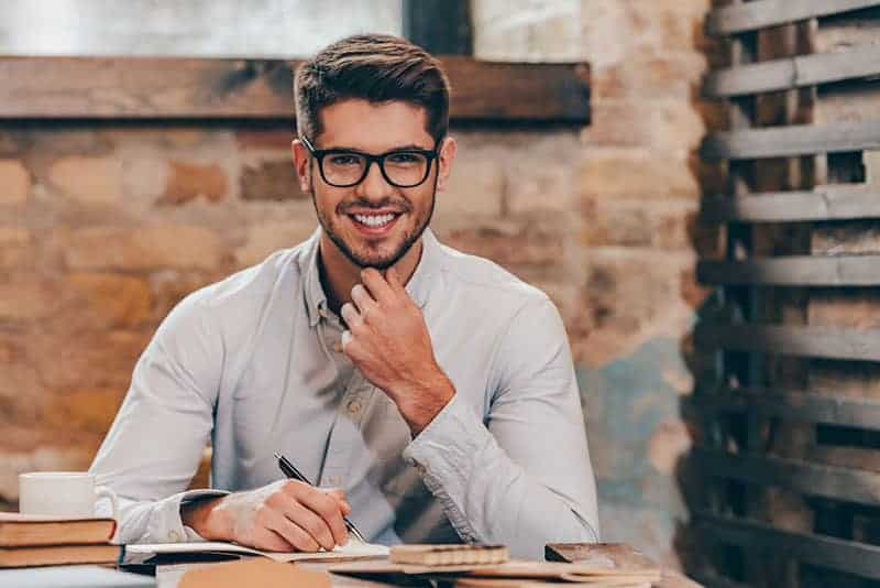young man wearing eyeglasses while holding a pen