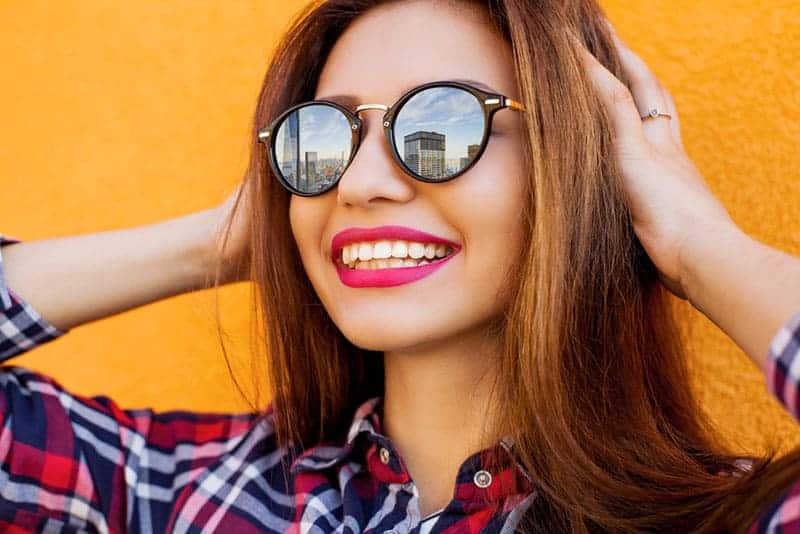 young smiling brunette wearing sunglasses outside