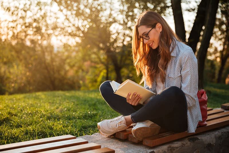 young woman reading a book on the bench