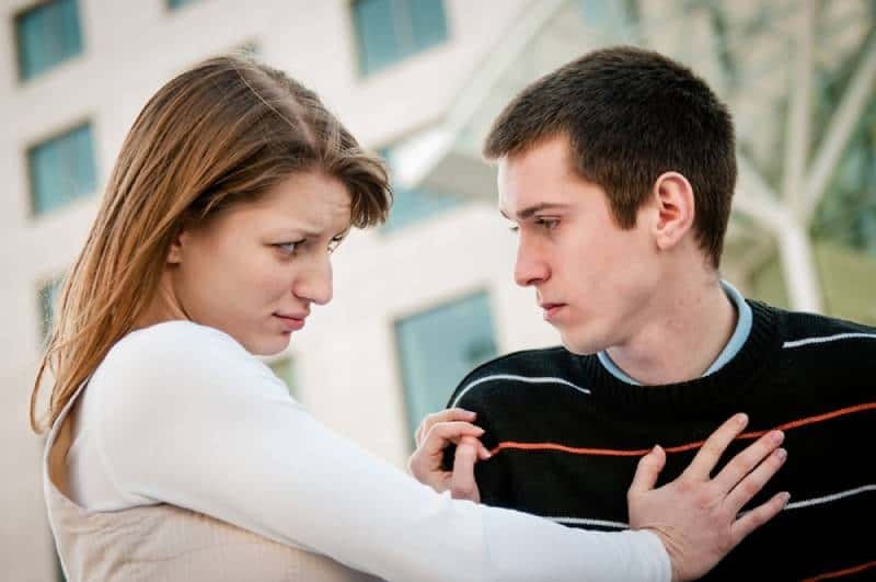 young woman refusing a man outside on the street having relationship problems
