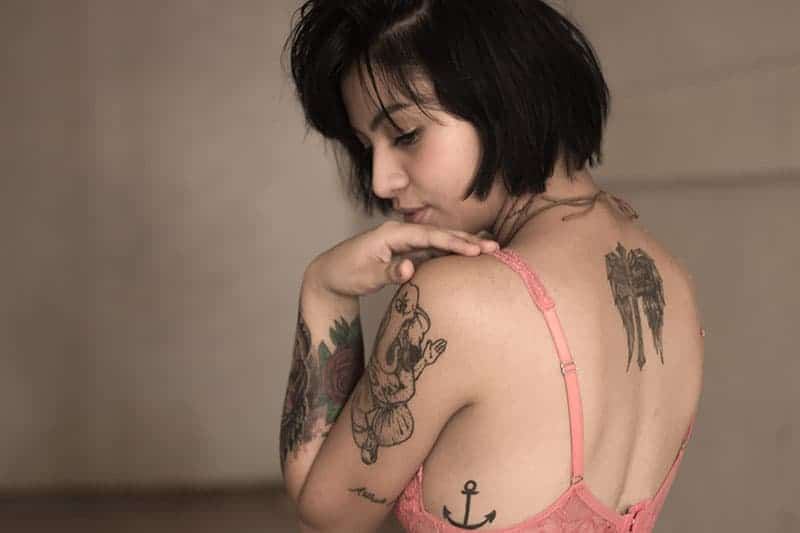 young woman wearing bra having tattoo