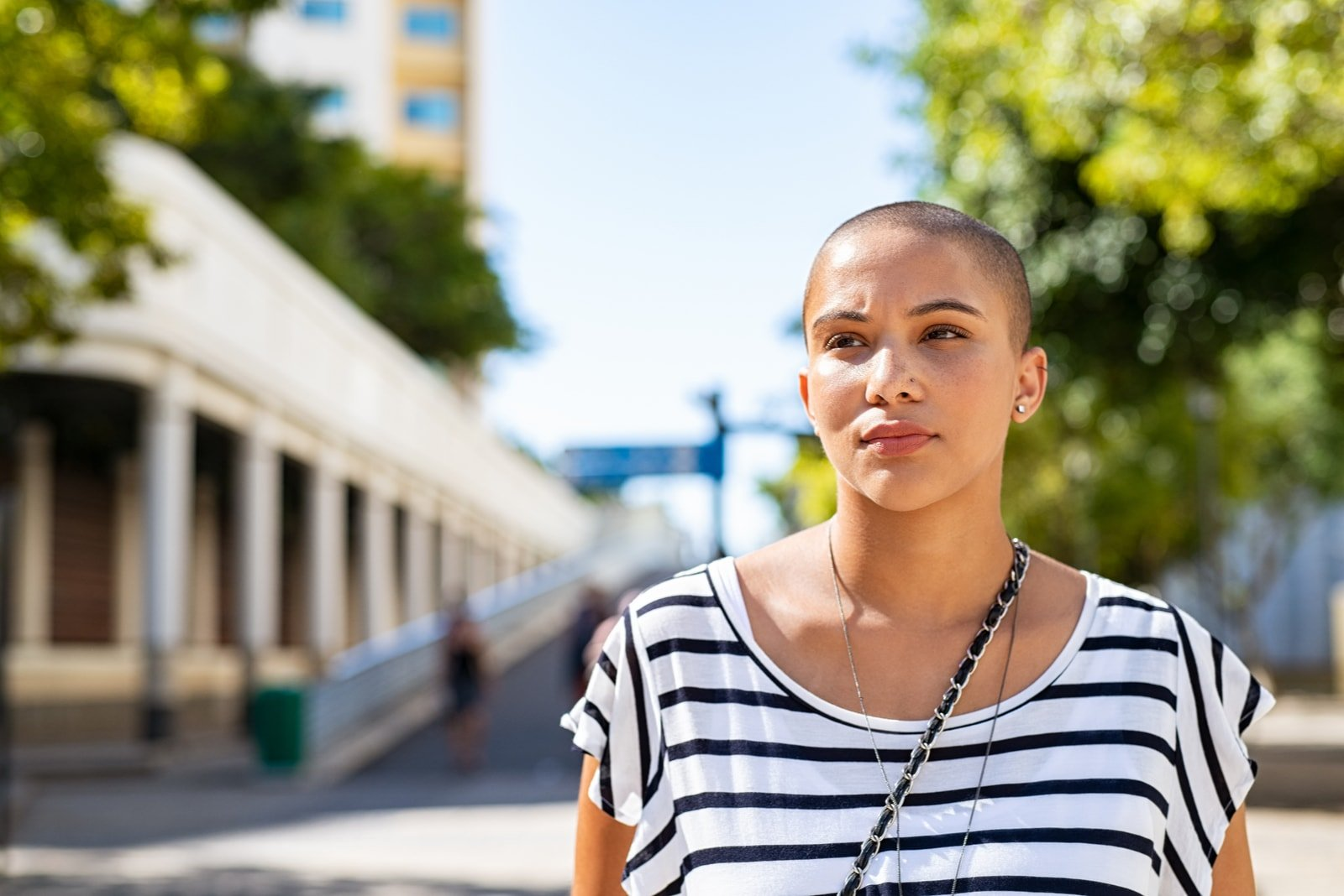 young woman with bald hair lost in deep thoughts
