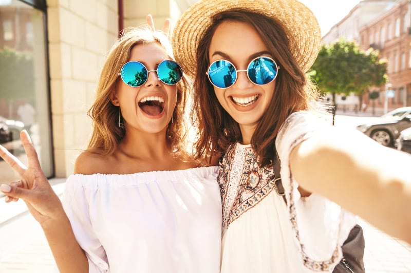 smiling two female with sunglasses taking selfie