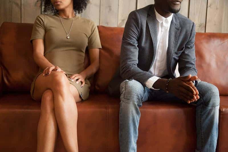 African american unhappy couple sitting on couch after quarrel fight