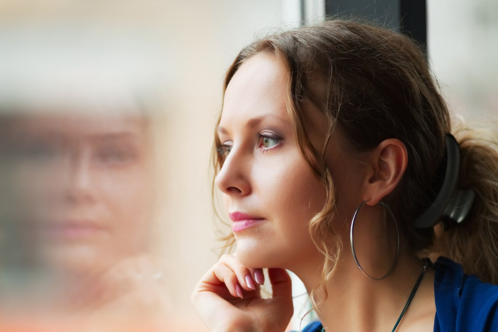 Sad beautiful woman looking through a window