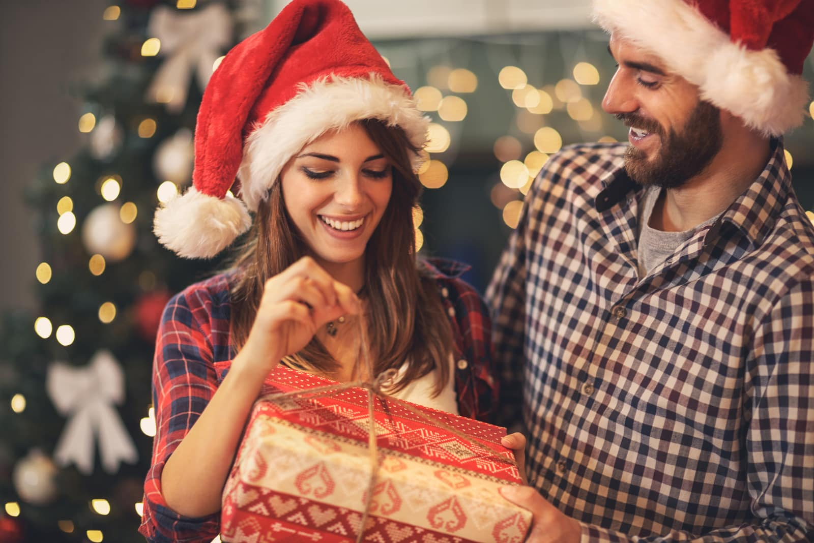 a happy couple opens a Christmas present