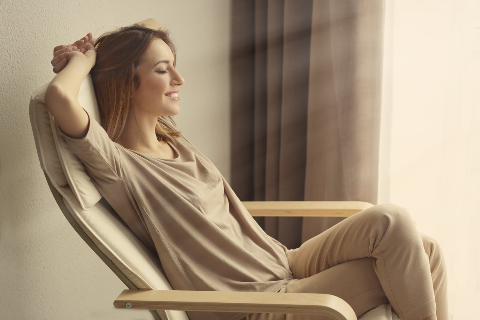 a beautiful smiling woman resting in an armchair