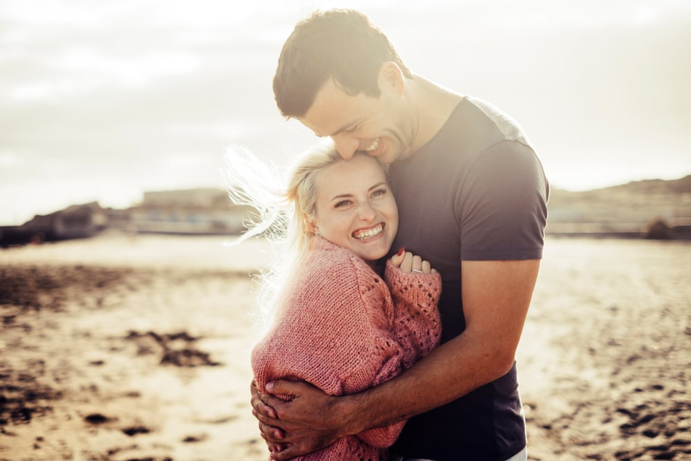 a beautiful young couple hugging on the beach