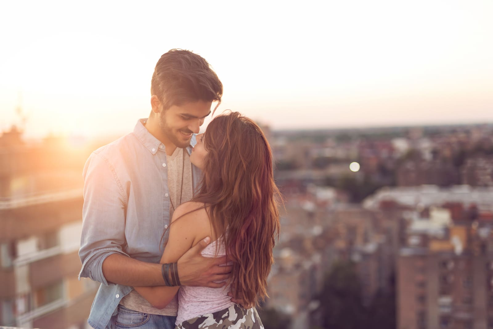 a loving couple hugging on the roof of a building