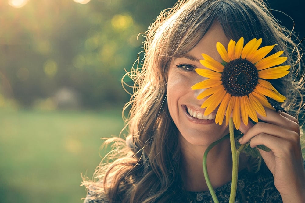 a portrait of a smiling girl holding a sunflower flower