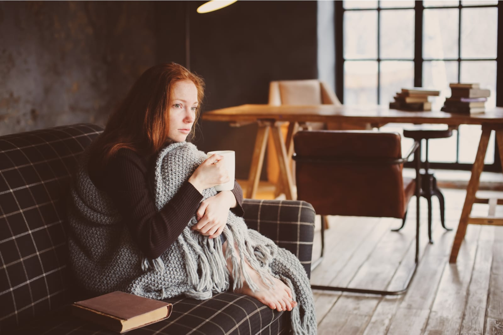a sad red-haired girl sits on the couch and drinks tea