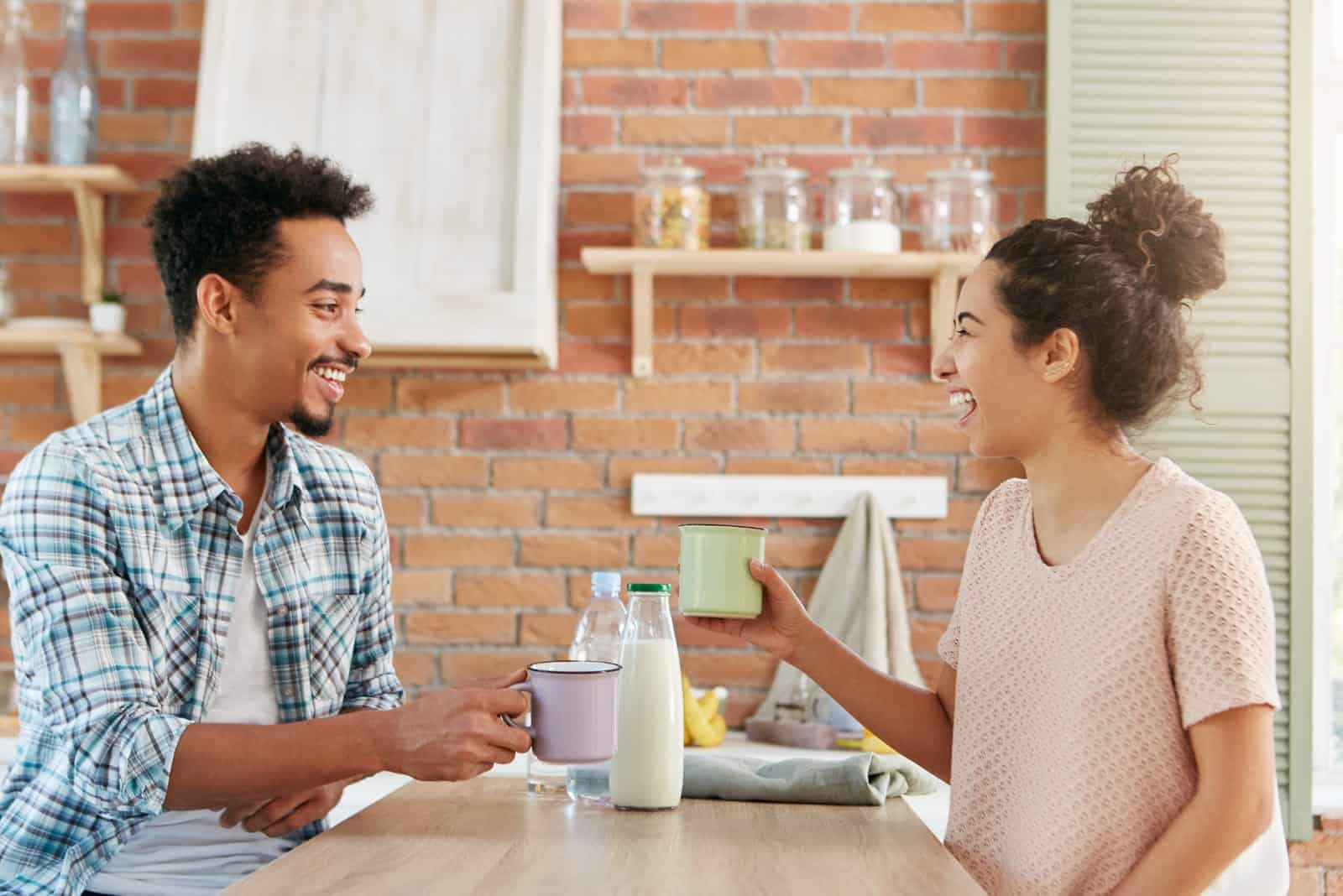 a smiling couple talking in the kitchen over breakfast
