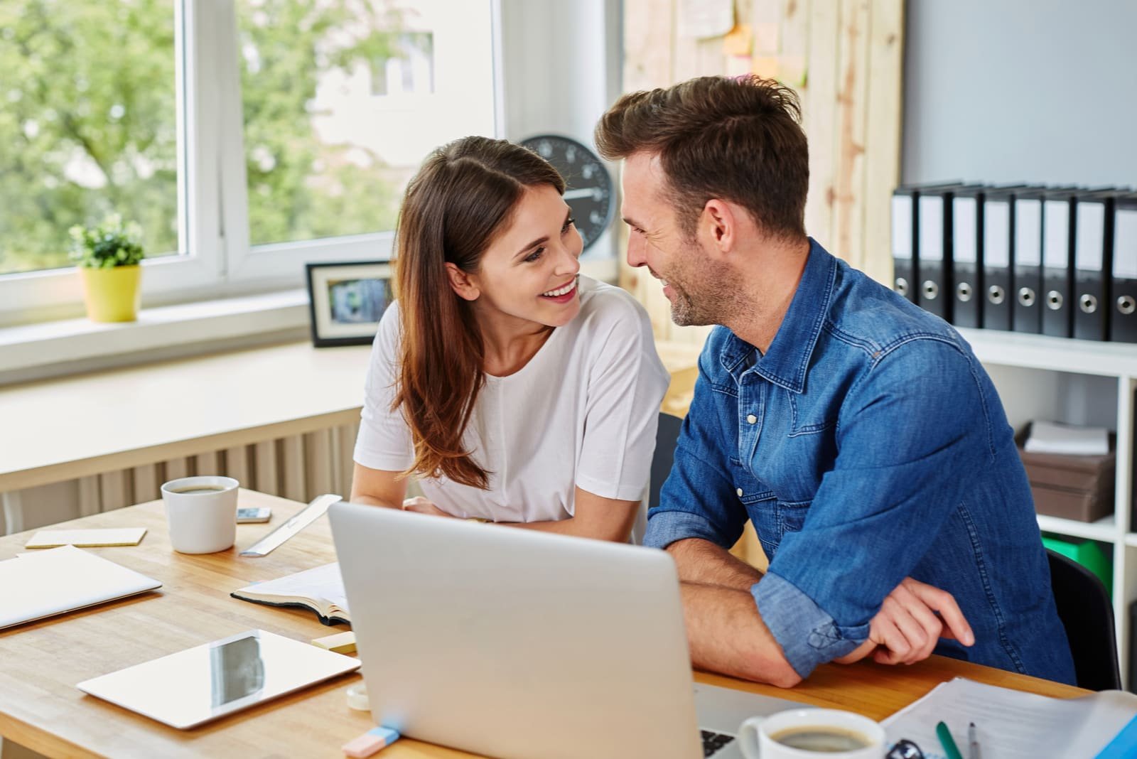 a smiling loving couple doing something on a laptop