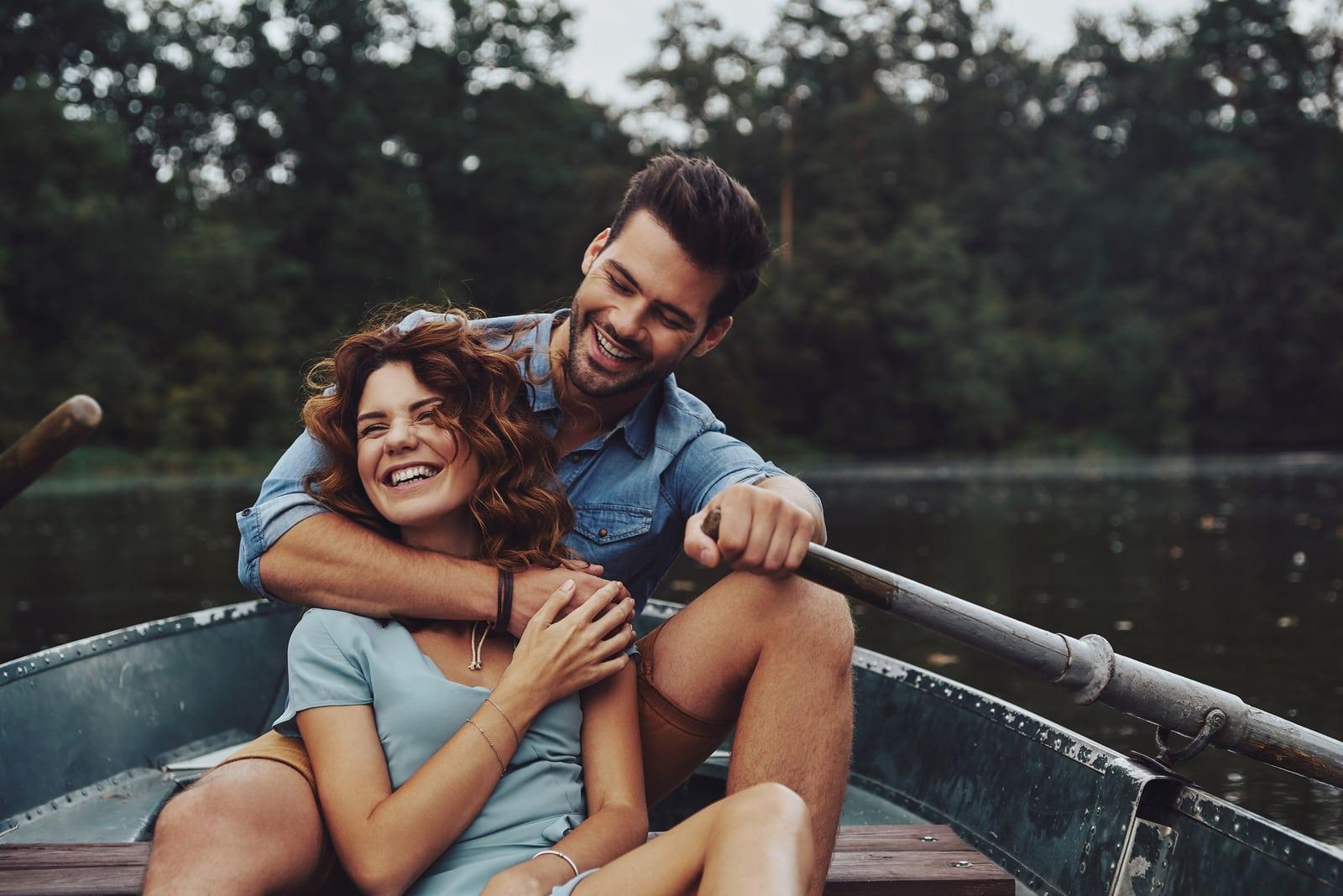 a smiling loving couple hugging and kayaking