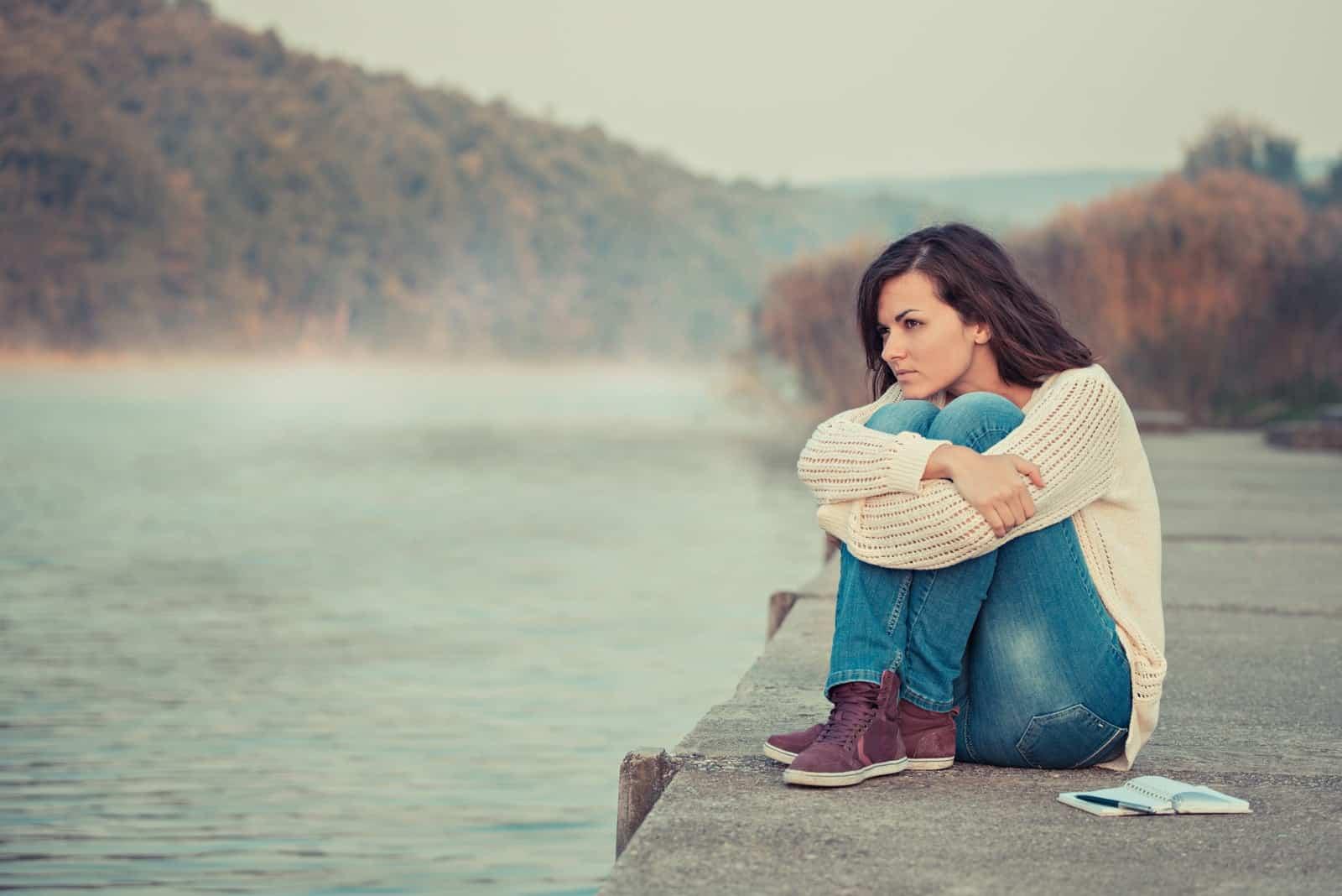 a woman sitting on a lake dock