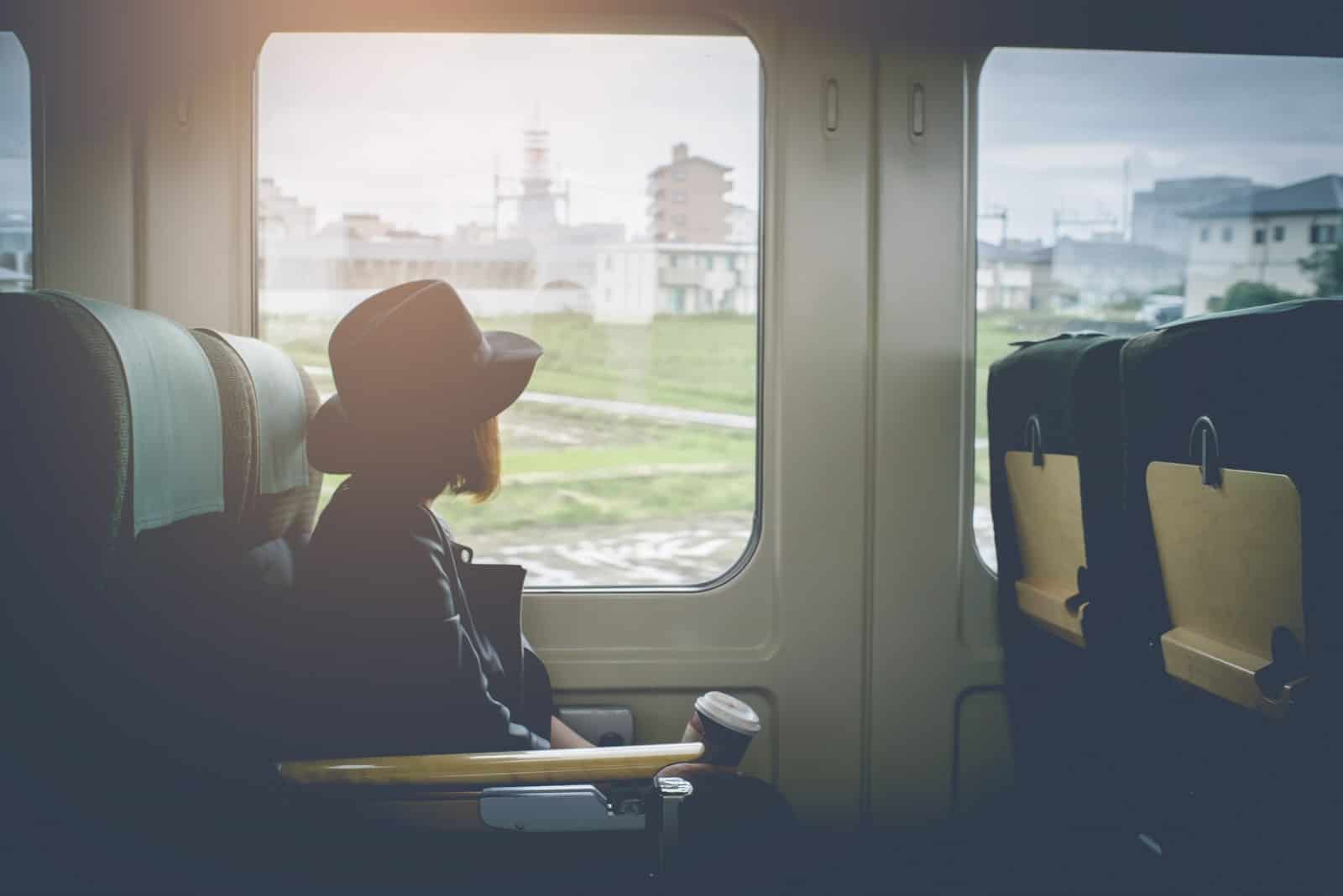 a woman with a hat travels by train