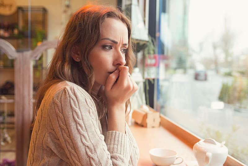 anxious woman sitting in cafe