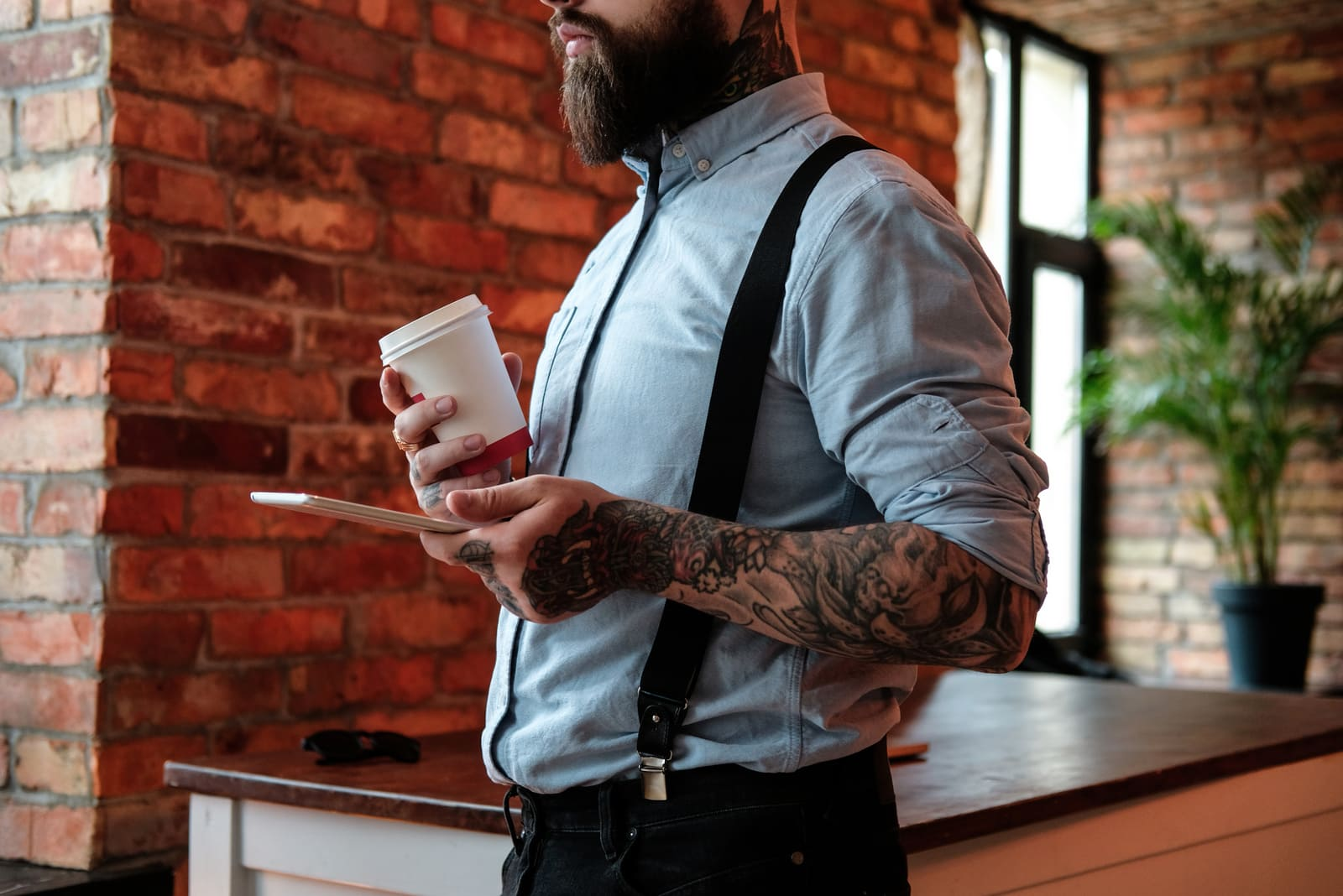 bearded man holding coffee and his phone