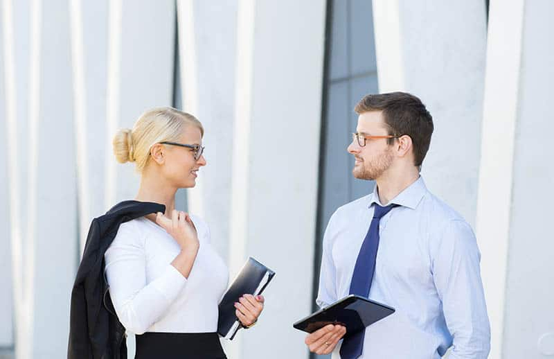 business man and woman talking outside
