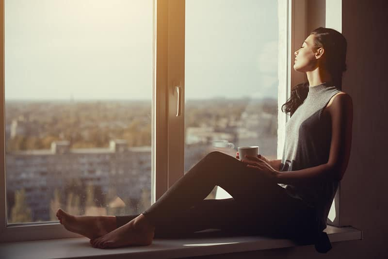 calm woman sitting by the window