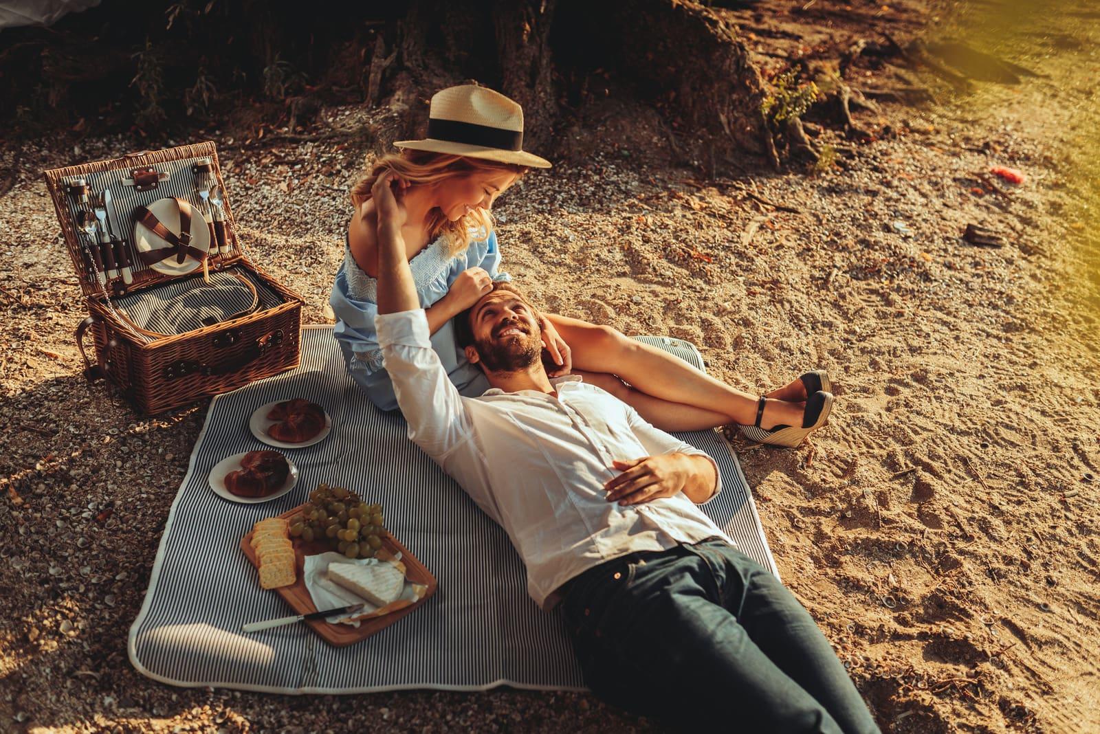 couple enjoying picnic time on the sunset