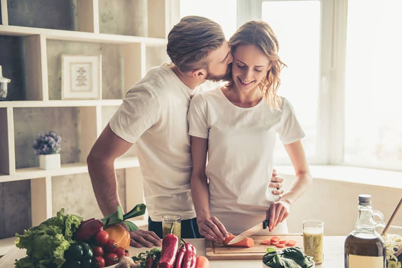 couple is talking and smiling while cooking food in kitchen