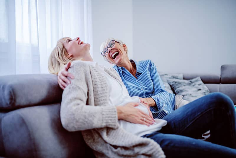 daughter and mother laughing on the couch