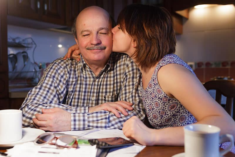 daughter kissing her dad in cheek