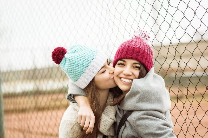 female friend kisses her best friend on cheek