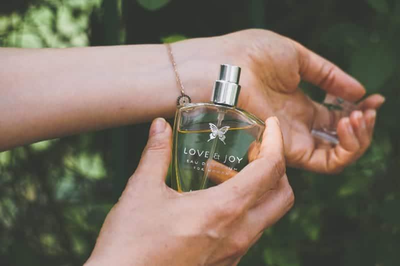 girl puts perfume on hand