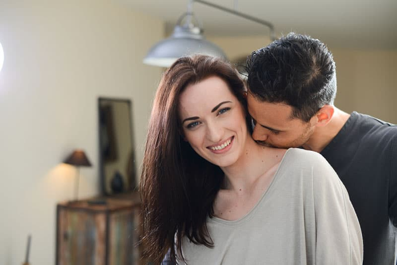 handsome young man kissing beautiful young girlfriend in her neck