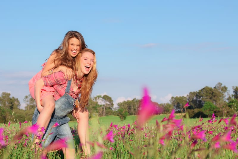 happy woman piggybacking her best friend