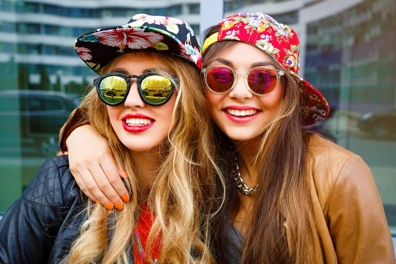 hipster female friends wearing cap and sunglasses