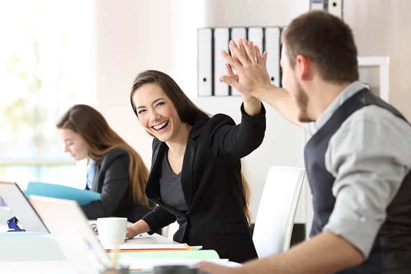 man and woman high five at office