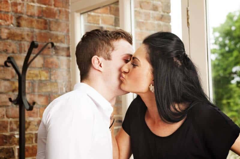 man and woman kissing on cheek