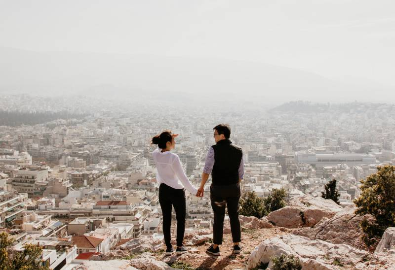 man and woman on top of hill holding their hands