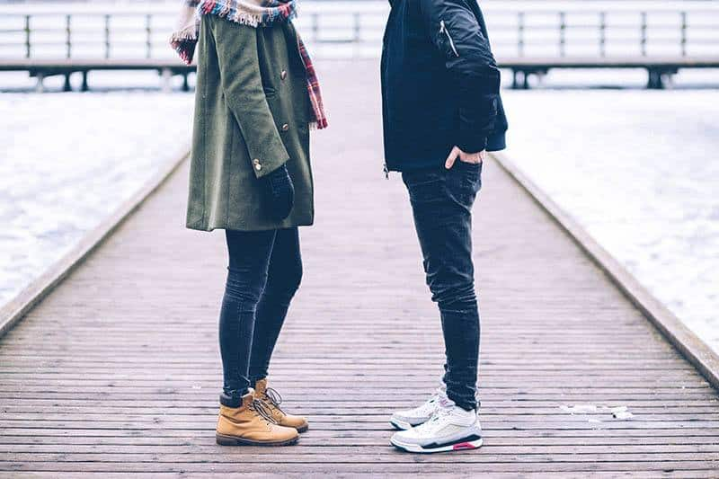man and woman talking outside during winter