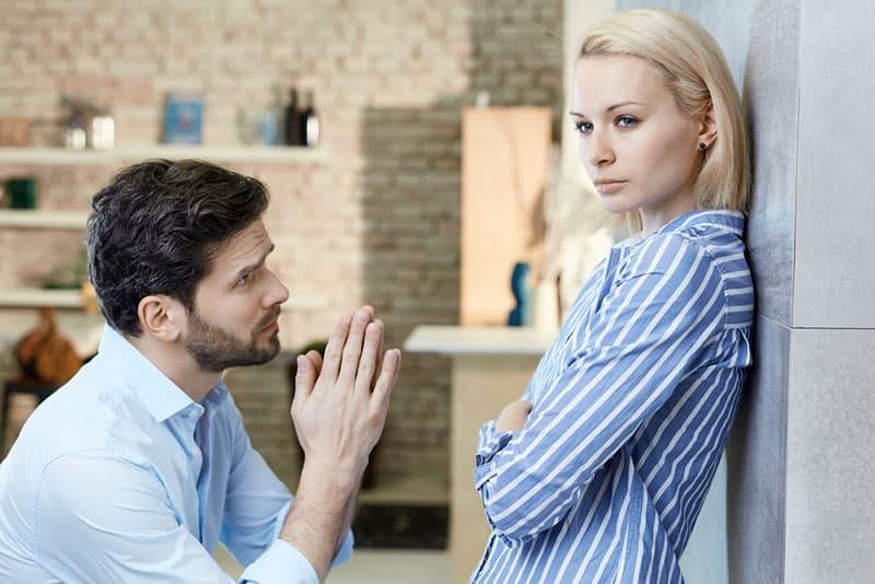 man begging woman