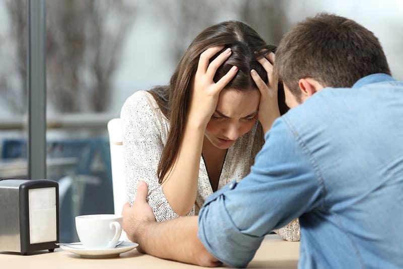 man comforting crying woman