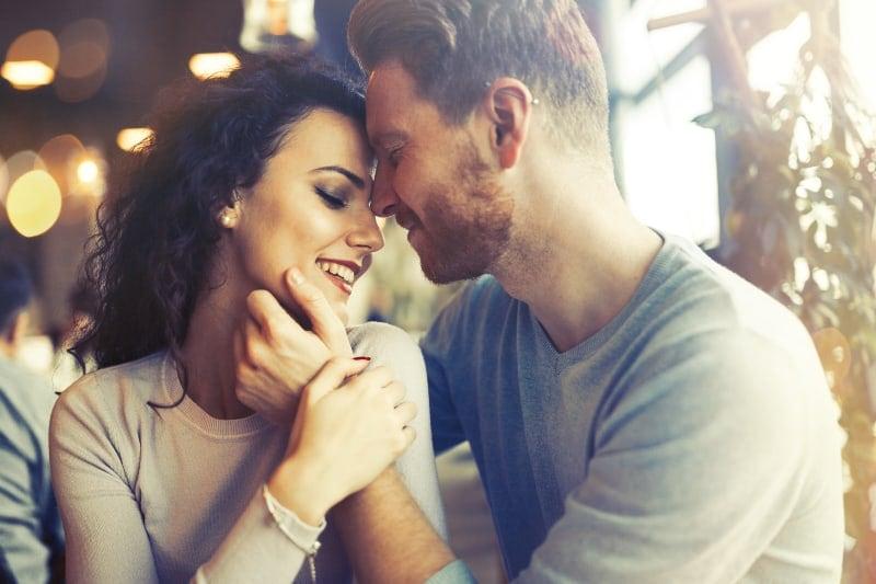 man cuddling woman for cheeks