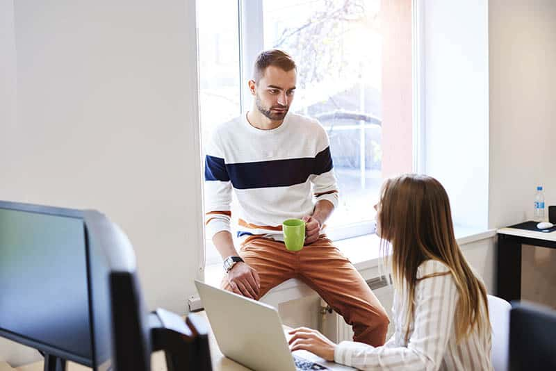 man holds cup of tea and talking to woman