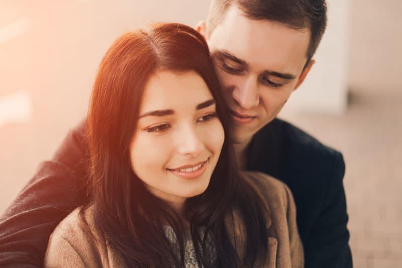man hugging young woman