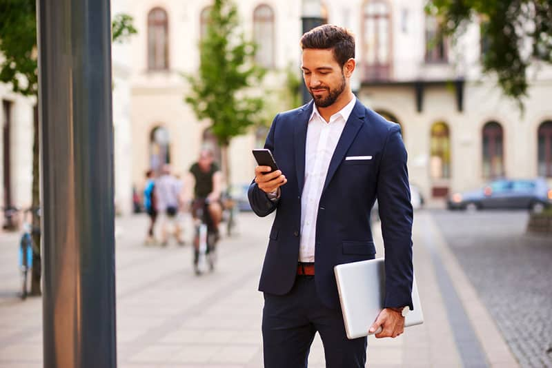 man in suit typing on phone