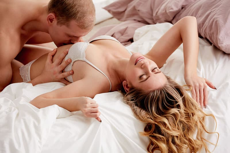 man kissing woman stomach in underwear on bed