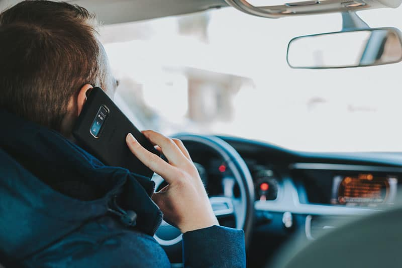 man talking on phone in the car