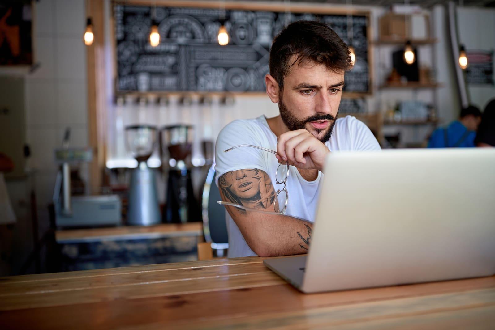 man wearing white t-shirt sitting in cafe