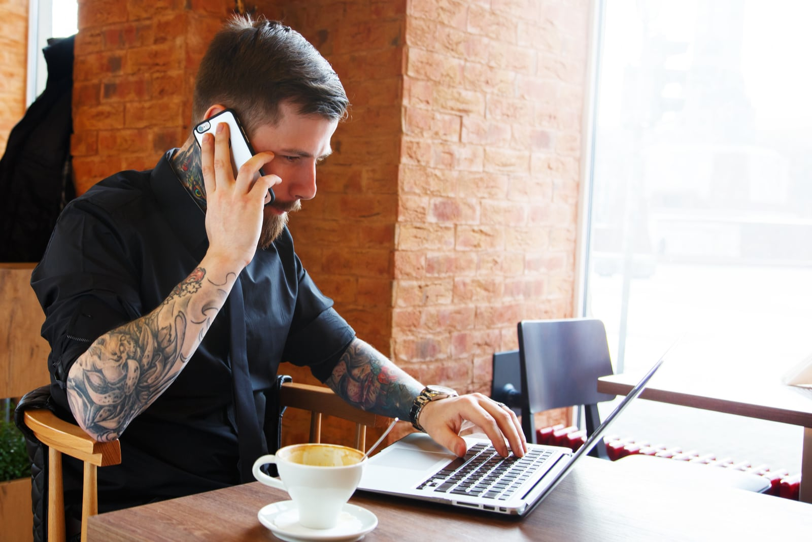 man working on laptop and talking on his phone