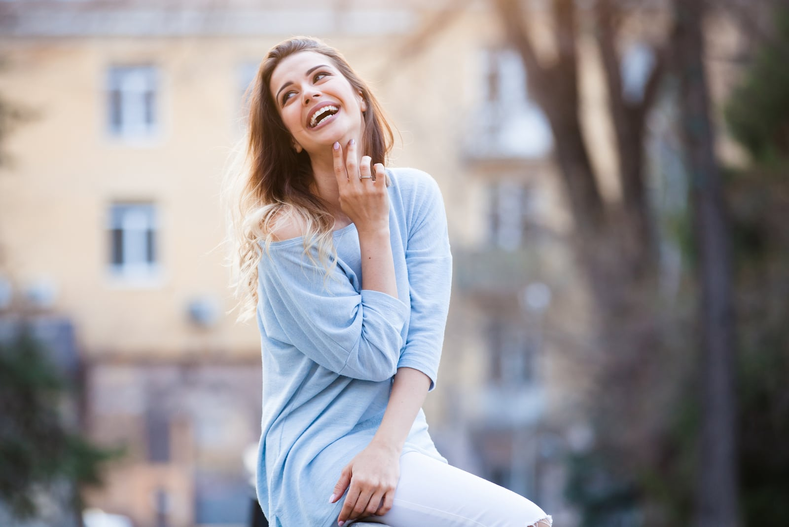 outside on the fence sits a smiling woman
